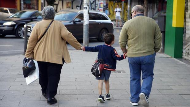Dos abuelos acompañan a su nieto a la escuela