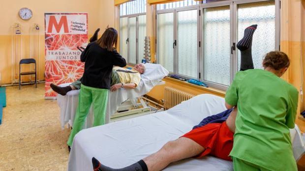 Dos fisioterapéutas de la Asociación Esclerosis Múltiple Valladolid durante una de las sesiones de rehabilitación que desarrollan en sus instalaciones