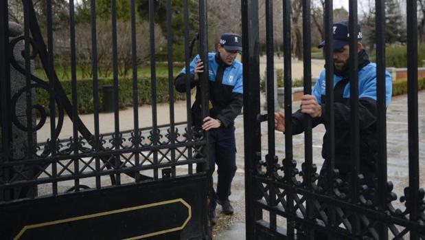Dos agentes cierran una de las puertas del parque del Retiro