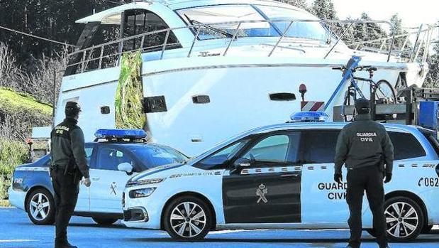 Agentes de la Guardia Civil custodian el cuerpo de la víctima que cuelga del yate