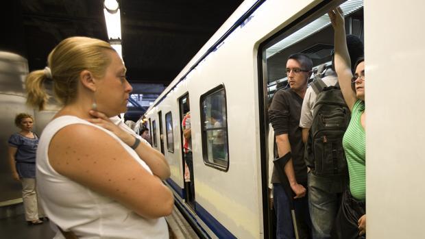 Una mujer espera en el andén ante la multitud de viajeros que copa el vagón