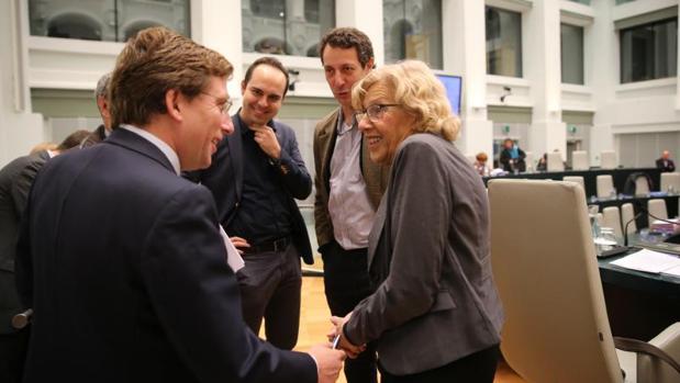 El portavoz del PP, José Luis Martínez-Almeida, charla con la alcaldesa Manuela Carmena, antes de que comience el Pleno
