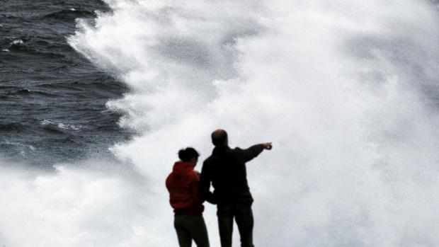 Dos personas el pasado sábado observando el oleaje en Muxía durante el paso de la borrasca Félix