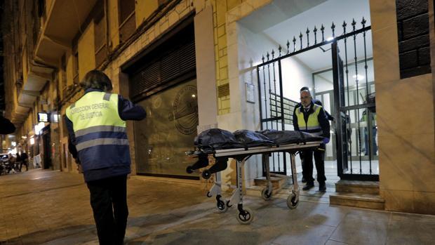 Miembros del Retén Funebre y agentes del Cuerpo Nacional de Policía retiran los restos humanos hallados en el interior de una vivienda situada en la calle de Vicente Zaragozà del del barrio valenciano de Benimaclet