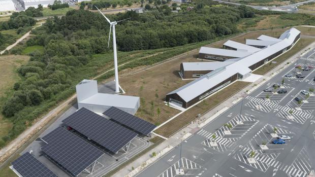Vista aérea del edificio, donde se distinguen las plantas fotovoltáicas y el aerogenerador