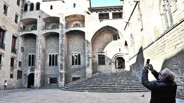 Un turista fotografía la plaza del Rei en Barcelona