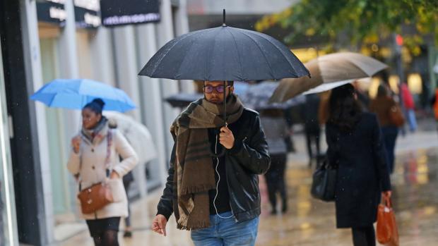 Varias personas se protegen de la lluvia en una imagen de archivo tomada en el centro de Valencia