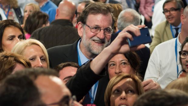 Mariano Rajoy se fotografía con un grupo de personas antes de la Convención Nacional del PP en Sevilla