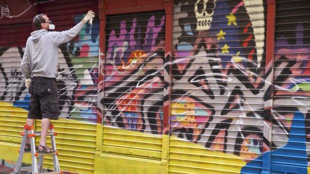 Un grafitero pinta el cierre de una tienda, durante la edición anterior