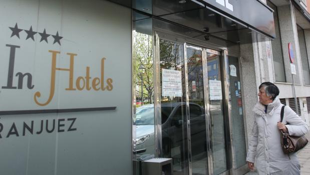 Una mujer mira la entrada del hotel All In, cerrado en Aranjuez