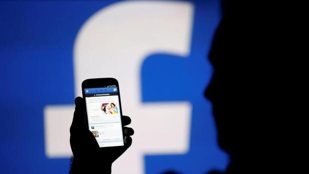 La silueta de un hombre viendo la aplicación de Facebook en su móvil