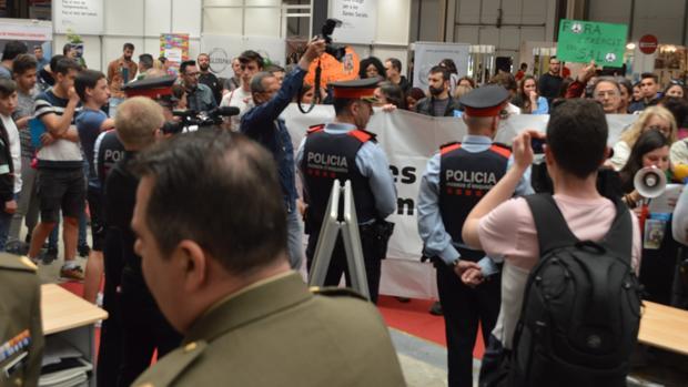 Los miembros de la plataforma Desmilitaricemos la Educación ante el «stand» de los militares