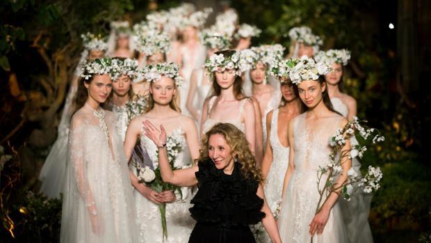 La diseñadora libanesa Reem Acra, junto a sus modelos, saluda tras el pase de sus vestidos