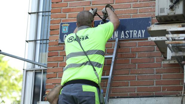 Un operario del Ayuntamiento de Madrid quita la placa de la calle dedicada al general Millán Astray