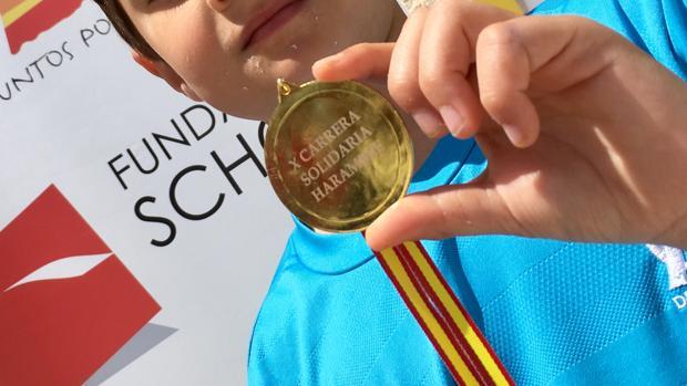 Uno de los niños participantes en la carrera con su medalla
