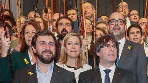 El exconsejero Antoni Comín, la expresidenta de la AMI Neus Lloveras, y el expresidente Puigdemont en un acto con alcaldes independentistas