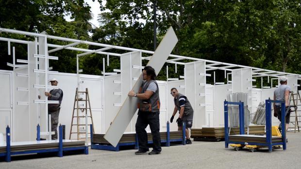 Los operarios montan las casetas de la Feria del Libro