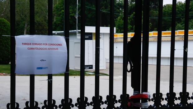 Las casetas de la Feria del Libro en El Retiro, tras un cartel que advierte del cierre