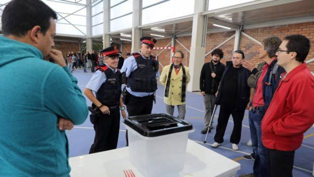 Varios Mossos esperan al recuento de votos para retirar las urnas durante el 1-O