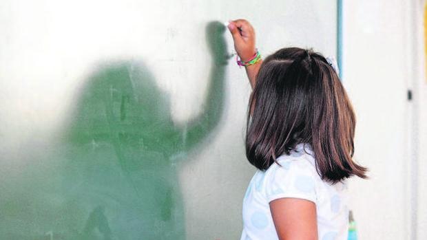 Imagen de archivo de una alumna escribiendo en la pizarra de un colegio
