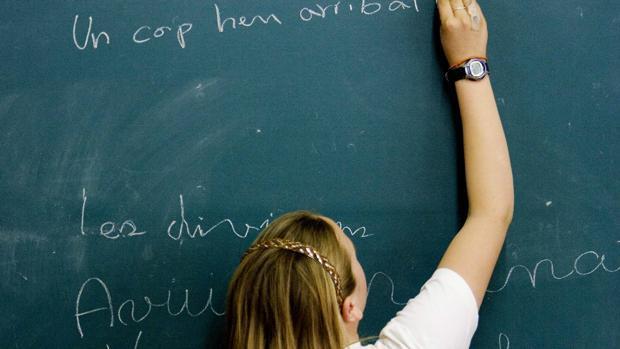 Una niña escribiendo en catalán en la pizarra de su clase