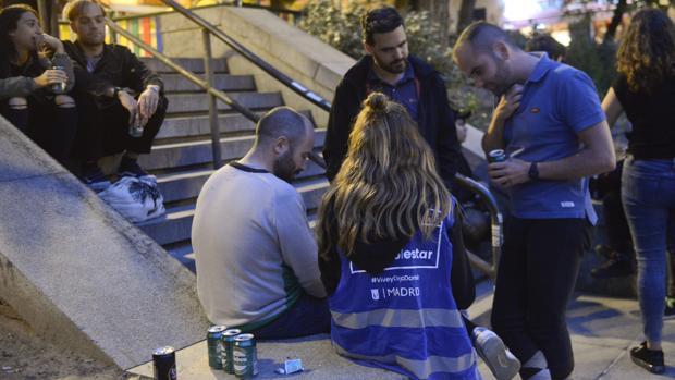 Una de las mediadoras sociales, charla con tres hombres en la plaza del Dos de Mayo