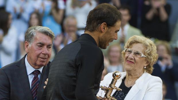 Manuela Carmena entrega el trofeo del Open de Tenis a Rafael Nadal, en presencia de Manolo Santana
