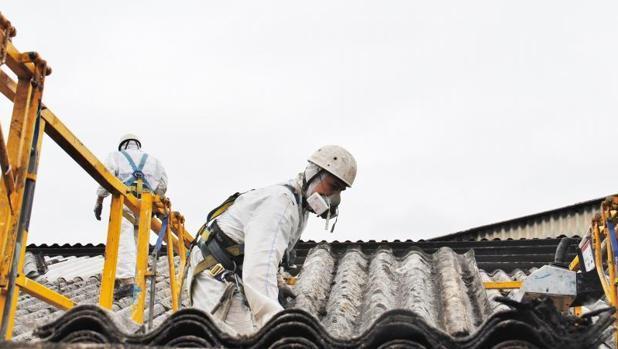 Operarios de una empresa especializada retirando un tejado de uralita