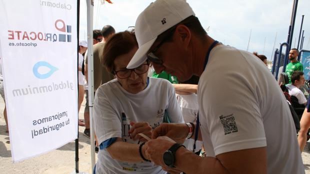 Una participante en La Mar Solidaria con su pulsera con código QR