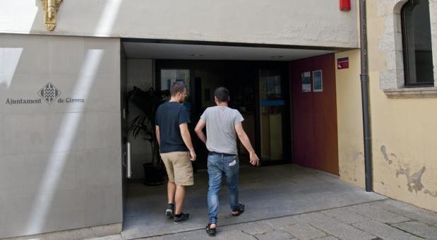Unos empleados entran este miércoles en el Ayuntamiento de Gerona, donde se personaron agentes de la Guardia Civil