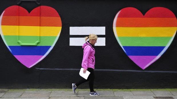 Una mujer camina por una pintada de apoyo LGTB