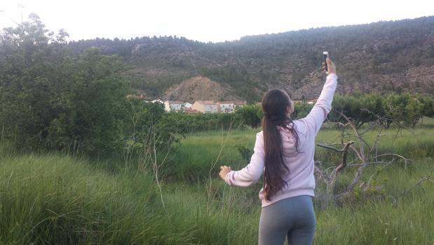Una vecina de Las Rinconadas busca cobertura móvil a las afueras de la aldea
