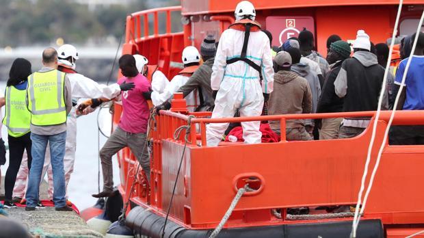 Autoridades y voluntarios de Cruz Roja ayudan a desembarcar en el puerto de ArguineguÍn, en Gran Canaria, a 152 personas que viajaban a bordo de un cayuco