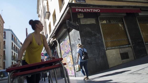 Una mujer mueve dos mesas ante el bar Palentino, en la calle del Pez de Malasaña