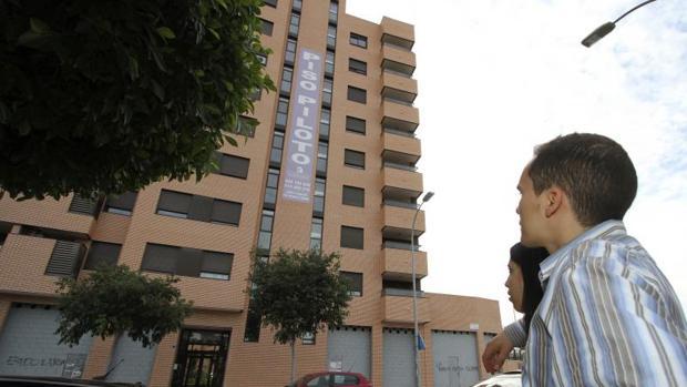 Una pareja mira el cartel de unos pisos en venta en Alicante