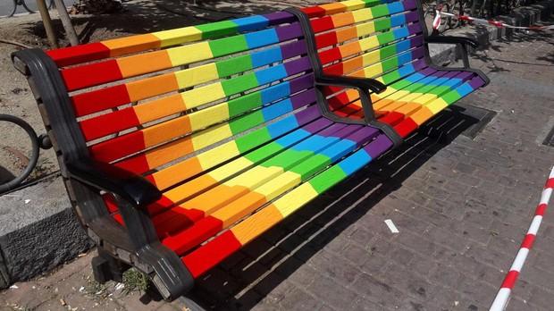Un par de bancos pintados con los colores representativos del Orgullo frente a la Junta Municipal de Puente de Vallecas