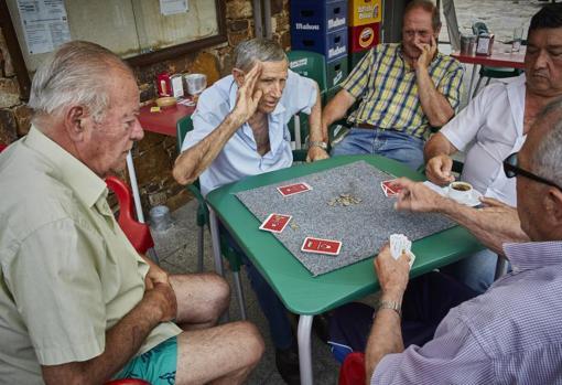 Un grupo de jubilados juega a las cartas en Aoslos, donde aún predomina la ganadería como actividad principal