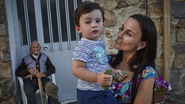 Ana sostiene en brazos a su hijo Daniel, de 2 años, con Pedro, de 100, detrás de ellos; son el más joven y el más viejo de Piñúecar
