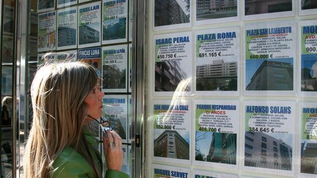 Anuncios de pisos en el escaparate de una inmobiliaria