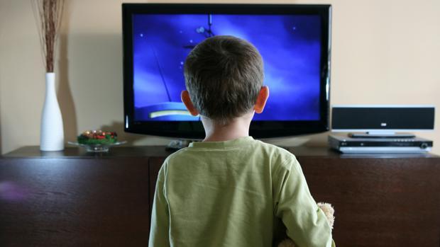 Un niño de 3 años viendo la televisión con un oso de peluche