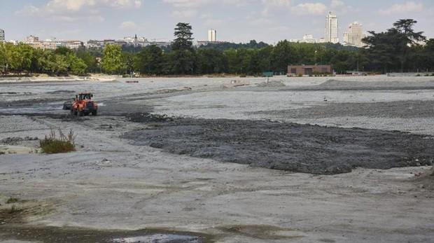 Una excavadora trabaja en el fondo del lago de la Casa de Campo, ayer