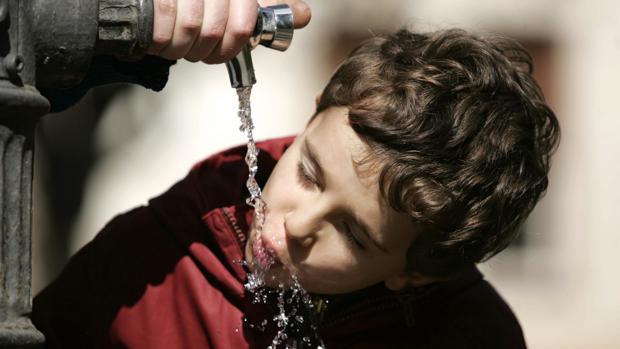 Un niño bebiendo agua en una fuente pública