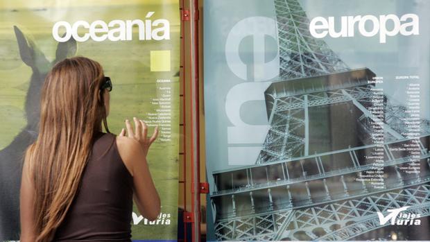 Imagen de una mujer delante de una agencia de viajes