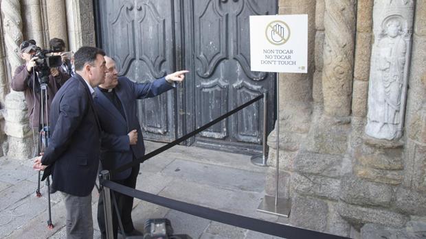 El conselleiro de Cultura y el deán de la Catedral obsrervan la pieza restaurada