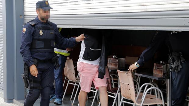 Agentes de la Policía Nacional acompañados en el registro por un detenido, inspeccionan un local de hostelería de Boiro