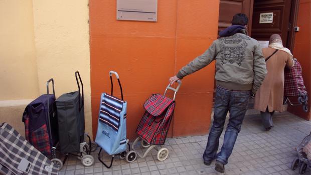 Personas sin recursos acudiendo a recoger comida a un centro asistencial de Zaragoza