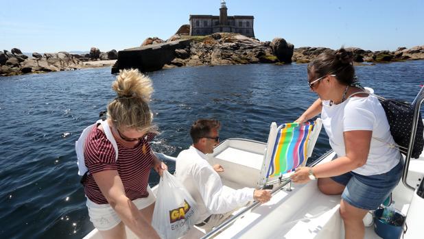 David Trillo, capitan del «Taximar» desembarcando con dos clientas en los alrededores de la isla Lobeira