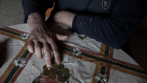Una persona recuenta unas monedas sobre el mantel