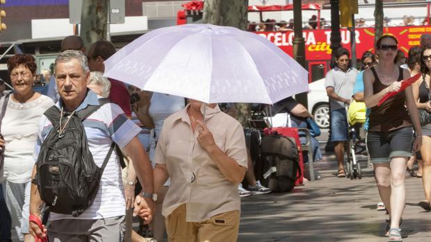 Una pareja bajo un paraguas por el centro de Barcelona