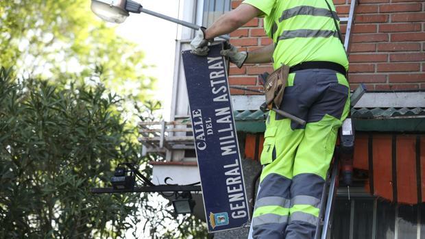 Un operario retira la placa de la calle de Millán Astray